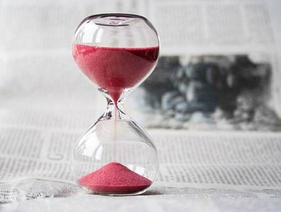 Red sand in an hourglass. Time may be ticking away, but that doesn't mean you have to mistime a stock market valuation.